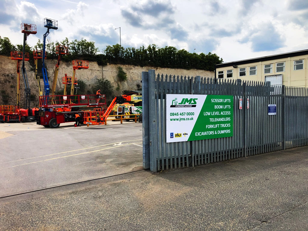JMS Dartford depot gate with view of machines
